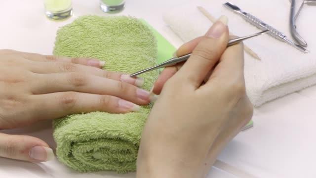 vidéos et rushes de manucure. repoussez la cuticule à l'égard d'un poussoir métallique. outils de manucure, vernis à ongles, huile. soins des ongles à domicile, spa, beauté. longs ongles naturels. salon de beauté. - cuticule