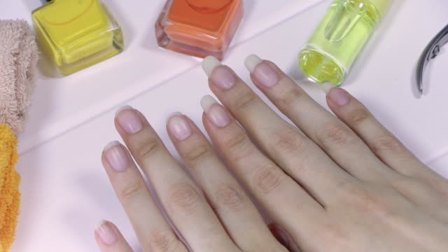 manicure. women's hands with short and long nails. natural long nails, unpainted. compare and choose the length of your nails. clean, beautiful, french manicure. home nail care, spa, beauty, salon. - ноготь на руке стоковые видео и кадры b-roll