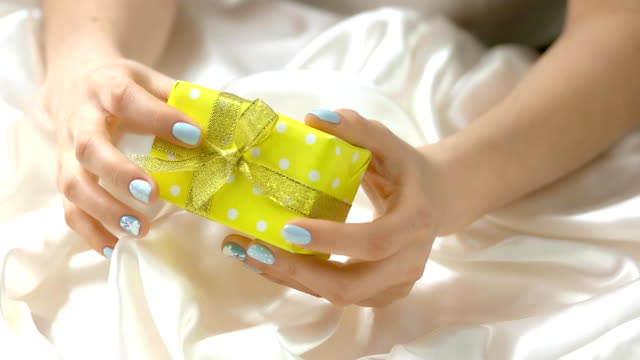 manicured hands holding little gift box. - аксессуар для волос стоковые видео и кадры b-roll
