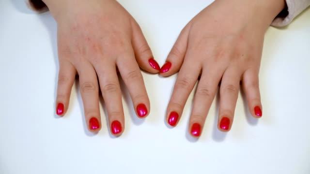 gepflegte hände am tisch im beauty-salon. frauen mit roten fingernägeln auf tisch klopfen - maniküre stock-videos und b-roll-filmmaterial