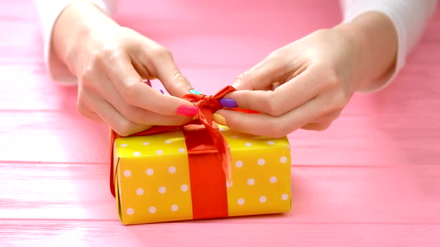 manicured hands ties ribbon on gift box. - nastro per capelli video stock e b–roll