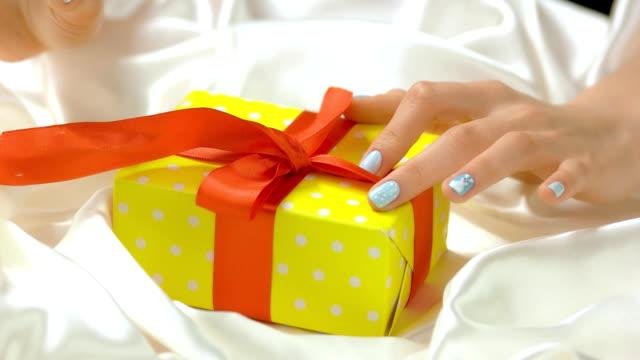 manicured hands untied ribbon on gift box. - аксессуар для волос стоковые видео и кадры b-roll