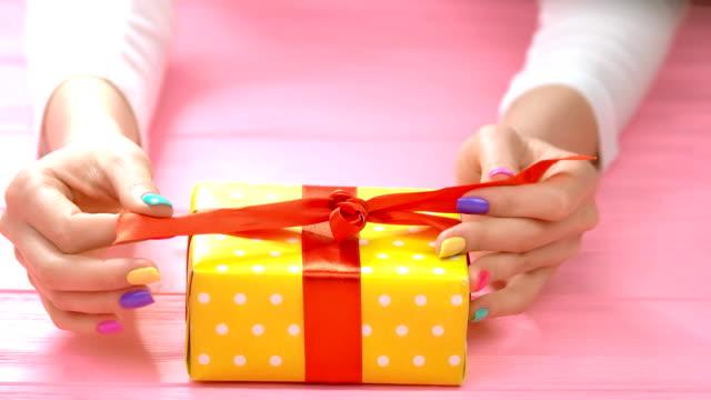 manicured hands untied ribbon on gift box. - nastro per capelli video stock e b–roll