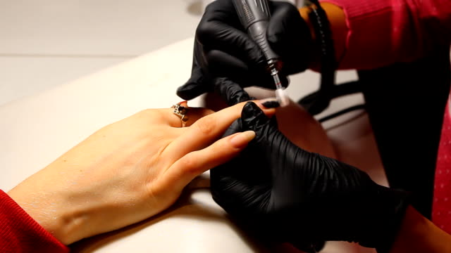 Manicurist Is Applying Electric Nail File Drill To Manicure On Female Fingers. video
