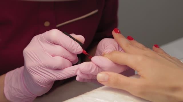manikyr polerar naglar med en kund i en skönhetssalong - nagellack bildbanksvideor och videomaterial från bakom kulisserna