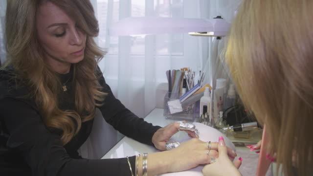 vidéos et rushes de manicurist scies surface de clous à femme attirante par lime à ongles dans le salon de beauté. feuille sur les ongles - cuticule