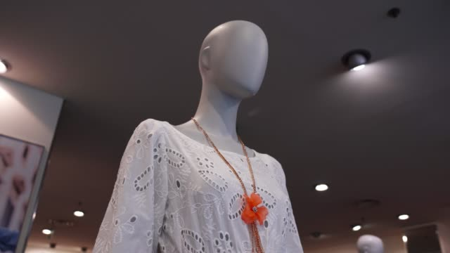 mannequin in white blouse and golden necklace with flower