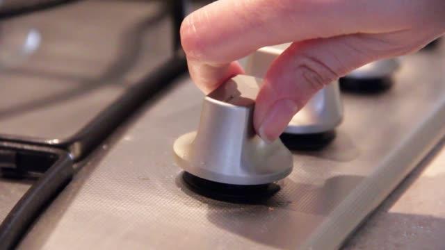 mano femminile che ruota la manopola dei fornelli in cucina per accendere il gas - fornello video stock e b–roll
