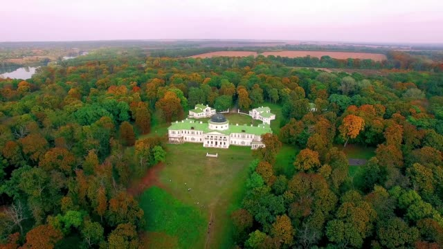 Manor in the autumn park at sunrise Aerial view of the Kachanovo manor at sunrise, aerial view of Manor on the lake shore in autumn, manor house in autumn forest on the lake mansion stock videos & royalty-free footage