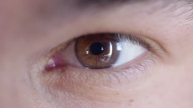 Man's brown eye looking at camera video