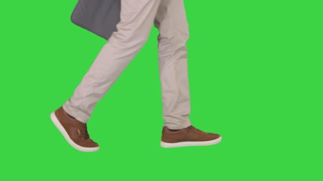 vídeos de stock e filmes b-roll de mans feet is walking in jeans and sneakers on a green screen, chroma key - perna