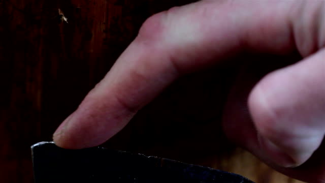 A mans finger is touching the blade of the axe video