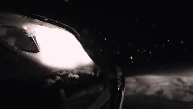 Mans hand cleaning car headlight from snow