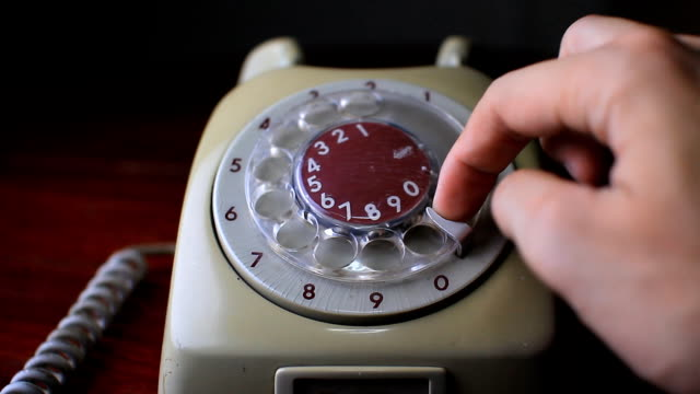 Man's hand dialing on an old fashioned vintage telephone.