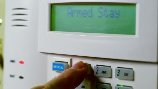 mans hand disarming a home security panel - niebezpieczeństwo filmów i materiałów b-roll