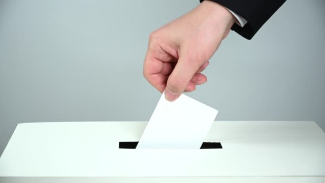 vidéos et rushes de main de l'homme vers le bas du bulletin de vote dans l'urne. - picto urne