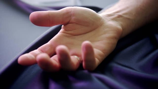Man's hand grabbing a crumpled striped bed sheet