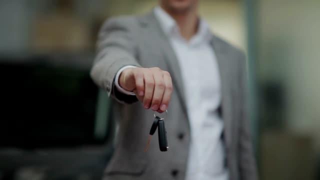 uomo mano di consegnare la chiave dell'automobile - chiave video stock e b–roll