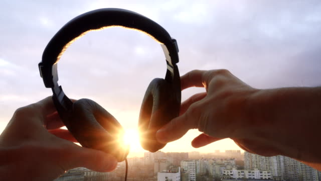 mans hand hold headphones at sunset city background. lens flare effect video