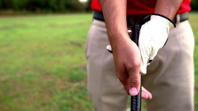 man's hand holding a golf club with a warm light at sunset - sprzęt sportowy filmów i materiałów b-roll