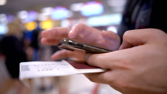 CU Man's Hand holding Boarding pass, Passport and Smartphone on his hand with airport counter checking background 4K CU Man's Hand holding Boarding pass, Passport and Smartphone on his hand with airport counter checking background passport stock videos & royalty-free footage