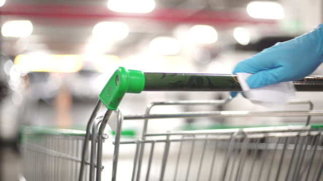 Man's hand in Glove wiping down door handles surfaces of the supermarket cart for cleaning curved-19 virus in the supermarket parking. 4K Video by CU Still Shot and selective focus with color grading. Use for background clip or insert shot of Man's hand in Glove wiping down door handles surfaces of the supermarket cart for cleaning curved-19 virus in the supermarket parking. cleaning stock videos & royalty-free footage