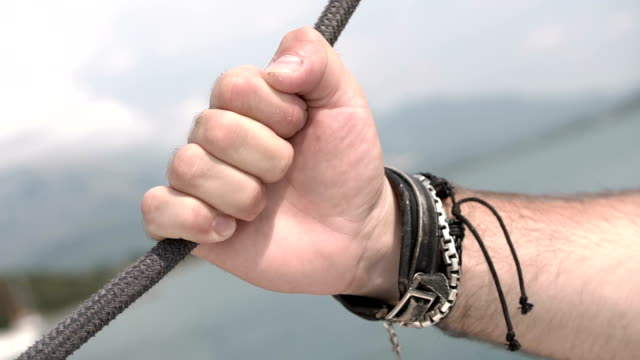 man's hand in leather bracelets holds onto sea rope of moving boat - браслет стоковые видео и кадры b-roll