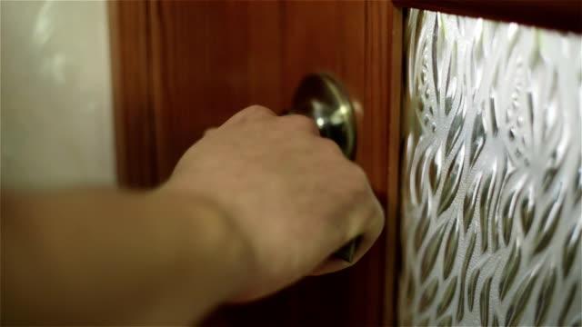 Man's hand is opening a wooden door. Man's hand is opening a wooden door. Man presses a golden metal doorknob. handle stock videos & royalty-free footage