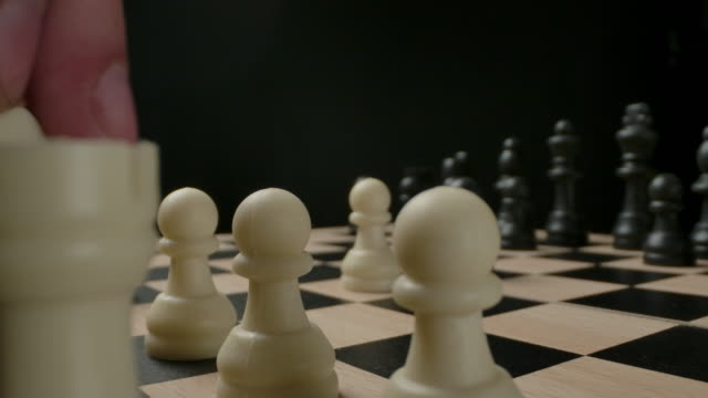 Man's hand moving chess figure knight from first line. Macro shot of small plastic chess