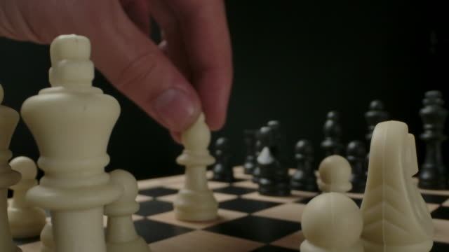 Man's hand moving white bishop chess piece from first line