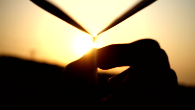 Man's hand of launch paper plane against the sun
