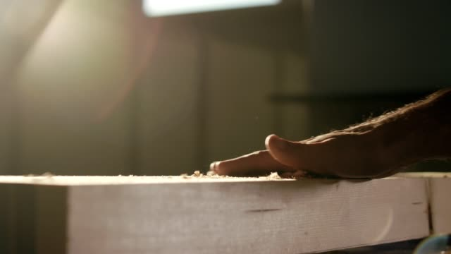 Man's hand over wood plank creating dust of wood chip particles
