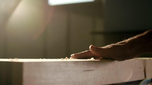 die hand des menschen über holzdiebe, die staub von holzspänenpartikeln erzeugt - bauholz brett stock-videos und b-roll-filmmaterial
