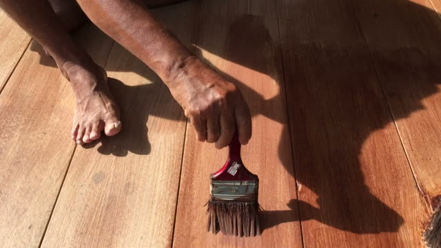 Man's hand painting wooden floor video