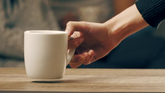 A man's hand placed a coffee cup on the table.