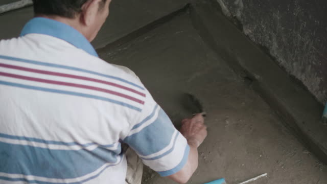 Man's hand plastering a floor with trowel. Construction worker at home. video