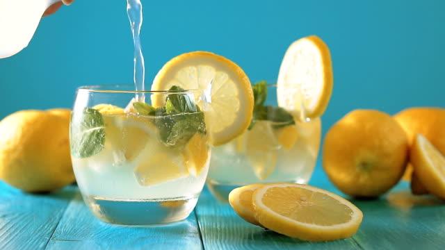 vídeos de stock e filmes b-roll de man's hand pours lemon juice from pitcher into glass - limonada tradicional