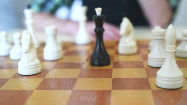 man's hand puts a white queen checkmate the black king video