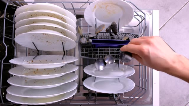 man's hand puts white dirty plates and spoon in dishwasher and pushes the basket with kitchenware. - struttura pubblica video stock e b–roll
