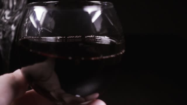 Man's hand rotates a glass of wine slow mo video