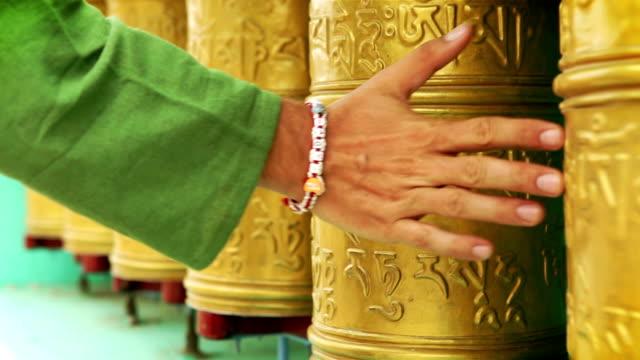 Man's hand rotating holy tibetan prayer wheels video