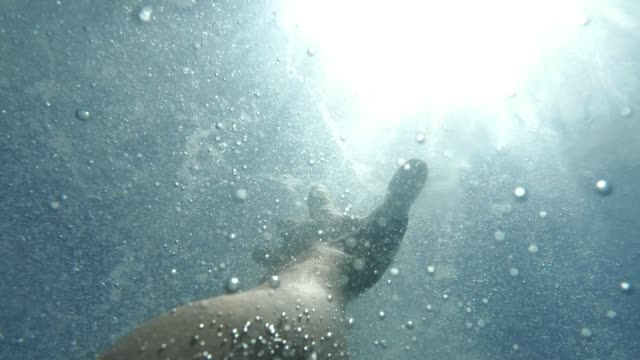 man's hand stretches underwater to surface of the sea. arm asking for help in air bubbles and trying to survive. point of view of man, drowning in deep ocean - fare la lotta video stock e b–roll