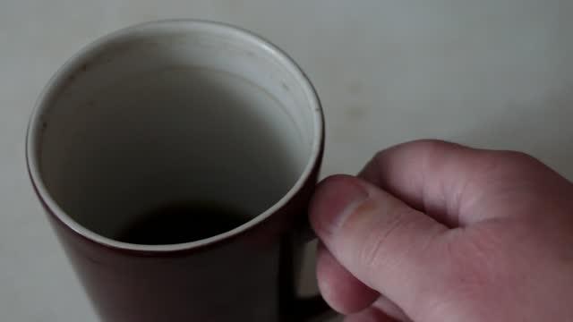 vídeos y material grabado en eventos de stock de la mano del hombre tomando una taza de porcelana marrón con café inacabado en la mesa. - imperfección
