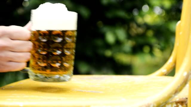 いい夏の暑い日に古い椅子からビールのガラスを取り男の手 - チェコ共和国点の映像素材/bロール