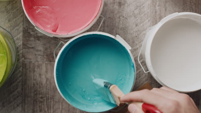 Man's hand taking paint from the bucket with paintbrush