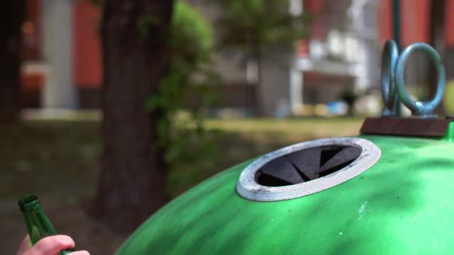 ręka człowieka wyrzuca pustą, szklaną butelkę w koszu na śmieci - odzyskiwanie i przetwarzanie surowców wtórnych filmów i materiałów b-roll