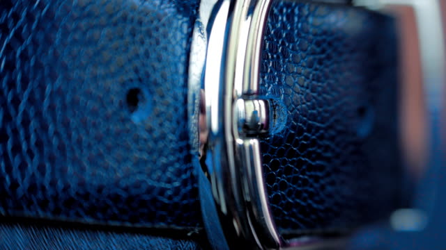 Man's hand tighten trendy leather belt with shiny buckle on a men's trousers video