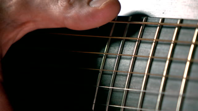 Man's hand touching guitar strings. Music performance. Super slow motion macro video video