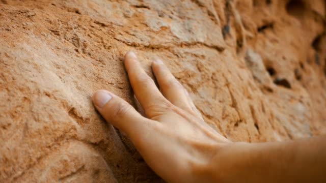 adamın eli eski duvara dokundu - kayaç stok videoları ve detay görüntü çekimi