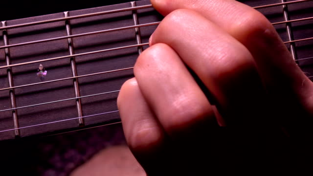 Man's hand touching strings on guitar fret. Music performance. FullHD macro video video